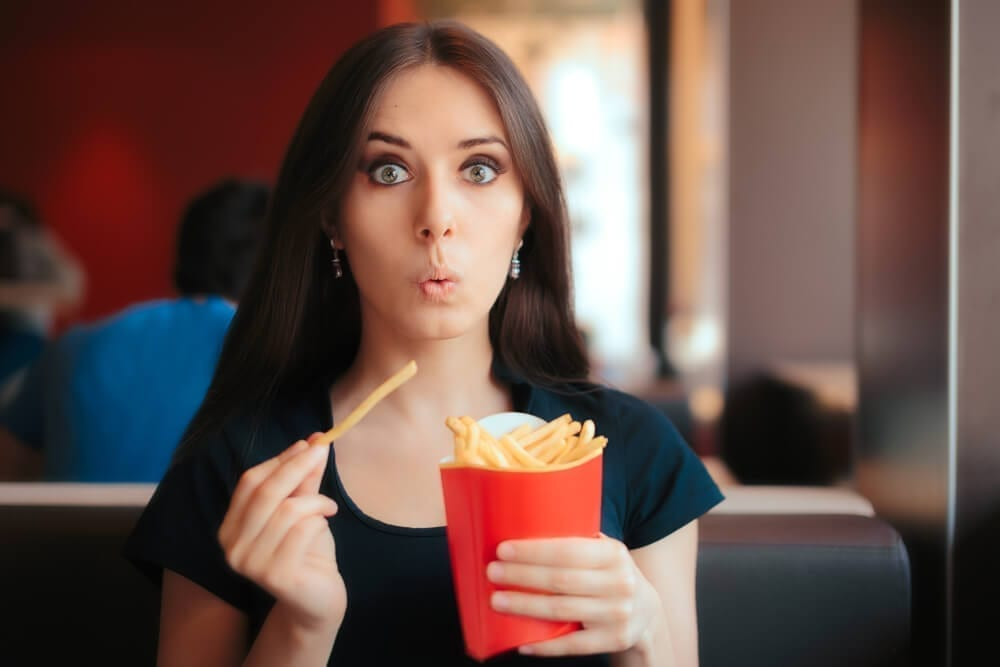 Hungry Girl Having Unhealthy Snack at a Dinner