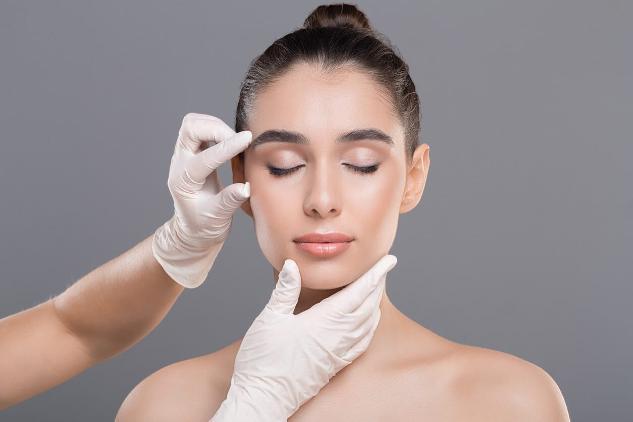 Cosmetologist Examining Facial Wrinkles On Young Woman Face