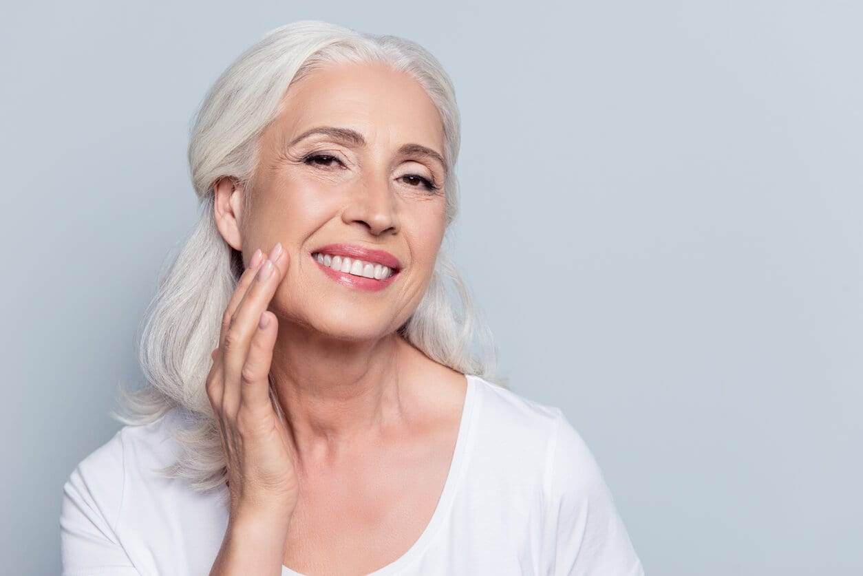 Charming, Pretty, Old Woman Touching Her Perfect Soft Face Skin With Fingers, Smiling at Camera Over Gray Background